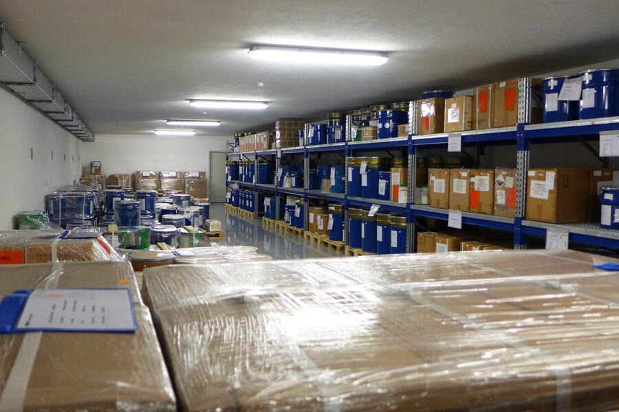 Blaue Fässer und braune Kisten stehen in Regalen.